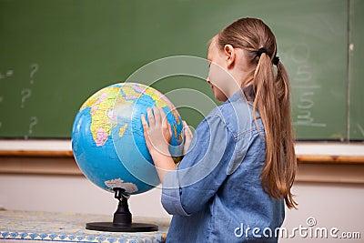 Focused schoolgirl looking at a globe