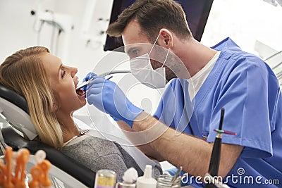 Focused stomatologist using dental drill and dental mirror Stock Photo