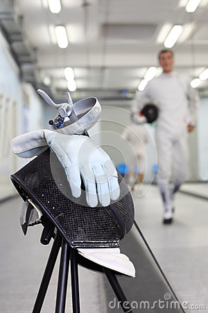 Foil, mask and glove at background ot fencer