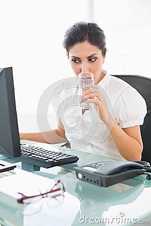 Fokuserad affärskvinna som dricker ett exponeringsglas av vatten på hennes skrivbord