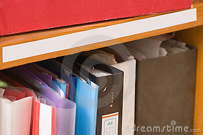 Folders with papers on a shelf.