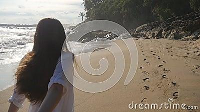 Folgen Sie mir, wie eine junge Frau ihren Freund an der Meeresküste anzieht Mädchen, die männlich sind und mit tropischem Exotik  stock footage