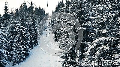 Folk som flyttar upp snöskogen på skidhissen lager videofilmer