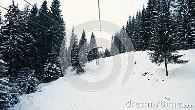 Folk som flyttar upp snöskogen på skidhissen arkivfilmer