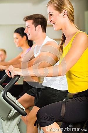 Folket i sportidrottshall på konditionen bearbetar med maskin