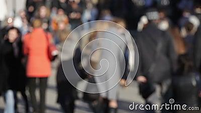 Folla della gente anonima che cammina sulla strada affollata
