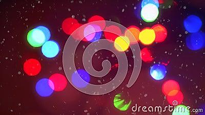 Fond coloré de bokeh de lumières de guirlande de Noël de clignotement de plan rapproché entouré par les flocons de neige en baiss clips vidéos
