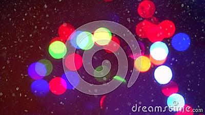 Fond coloré de bokeh de lumières de guirlande de Noël de clignotement de plan rapproché entouré par les flocons de neige en baiss banque de vidéos