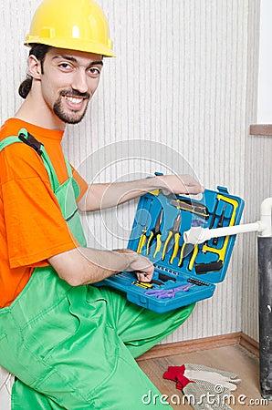 Fontanero que trabaja en cuarto de baño