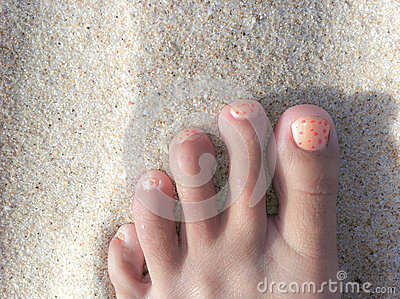 Foot on a beach with painted toe nails