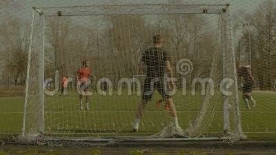Striker taking a shot on goal during football match stock footage