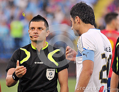 Romanian football referee throws the coin in order for the team to