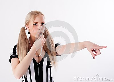 Football referee whistling and pointing to side