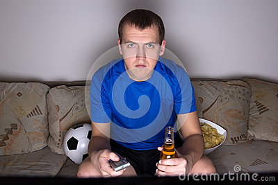 Football supporter in uniform watching tv