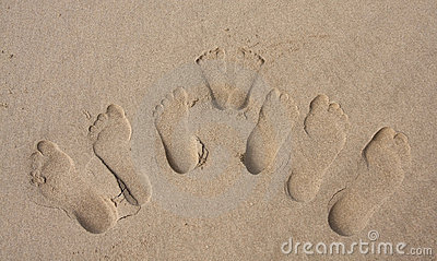 Footprints of a family in the sand on beach