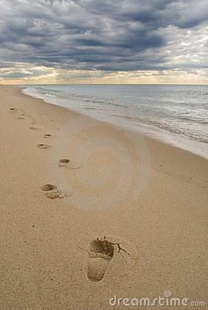 Footprints on a sandy beach, dark stormy clouds