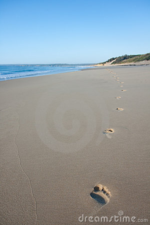 Footprints walking alone on secluded scenic beach