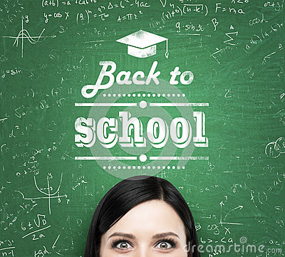 A forehead of the girl and words: ' back to school ' which are written on the green chalkboard. Stock Photo