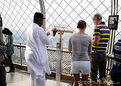 Foreign tourists with telescope on Eiffel tower Editorial Photo