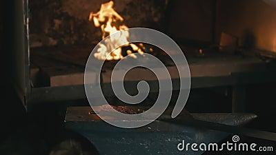 Forge workshop Fabricação manual Mãos de ferreiro com martelo ferrado em metal quente brilhante, na bigorna, a forja filme
