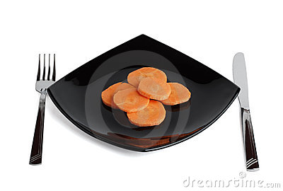 Fork, knife, black plate and carrot. Three.