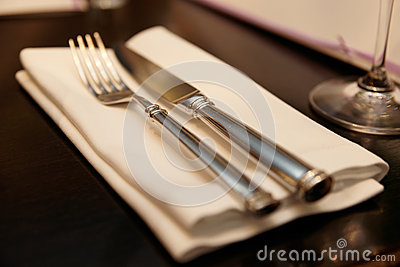 Fork, knife and napkin on restaurant table, warm light