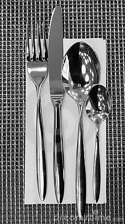 Fork, knife, spoons and napkin on restaurant table