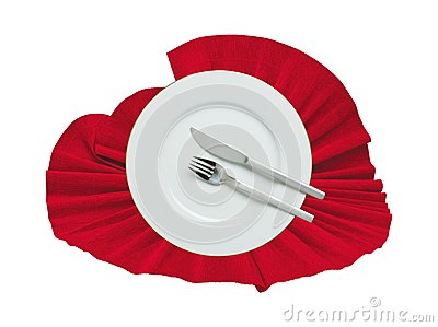 Fork, knife and white plate on a red cloth