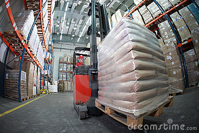 Forklift driver transporting sacks in warehouse
