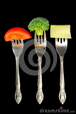 Forks with vegetables on a black background