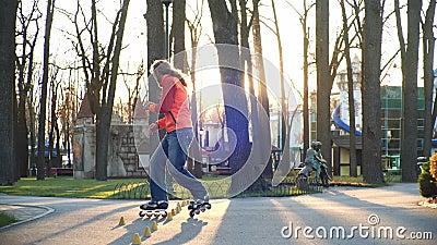 Formação de um rolo profissional que patina habilidosamente no parque central da cidade e faz turnos complexos video estoque