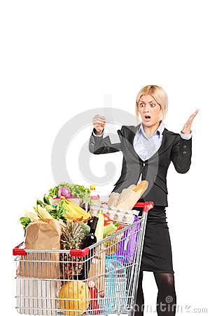 Formal woman looking at the shopping bill in disbelief