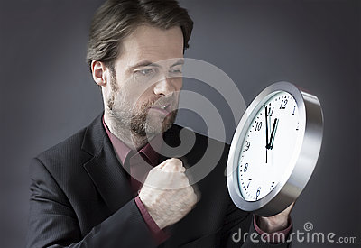 Office worker under time pressure punching clock with his fist