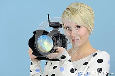 Fotógrafo de sexo femenino joven con la cámara de DSLR
