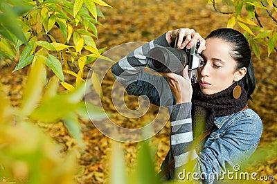 Fotógrafo hermoso de la muchacha en la naturaleza (en follaje)