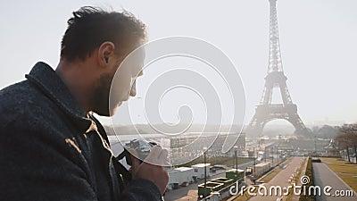 Fotógrafo independiente de visión trasera tomando una foto de la Torre Eiffel en París con cámara de película retro cámara lenta metrajes