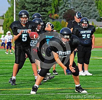 Fotbollquarterbacken för den amerikanska bollen mottar ungdommen Redaktionell Fotografering för Bildbyråer