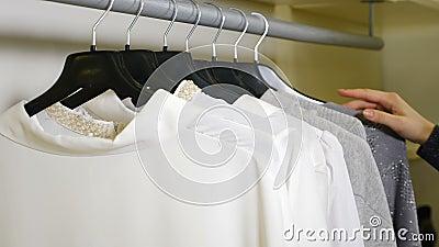 Foto di una donna che corre su rack per la ferrovia per Hangers e cerca indumenti al negozio di abbigliamento Acquisto stock footage