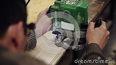 Foto do ombro das mãos de um artesão trabalhando com polimento com máquina de moagem manual em oficina de madeira video estoque