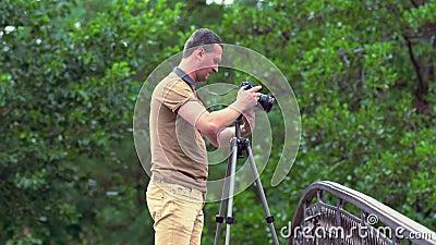 Fotograafvestiging zijn camera en driepoot stock video