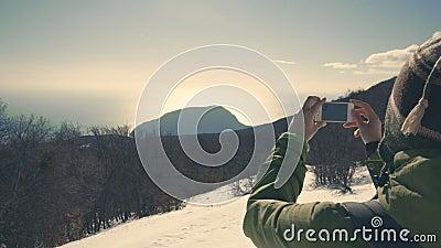 Fotvandrare som tar bilden av den lösa vinternaturen med hennes smartphone arkivfilmer