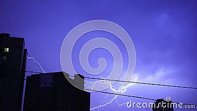 Foudre dans le ciel nocturne dans la ville, un éclair lumineux de lumière dans les nuages sous la pluie, un orage banque de vidéos