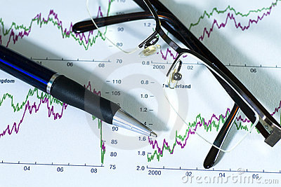 Fountain pen and glasses on stock chart.
