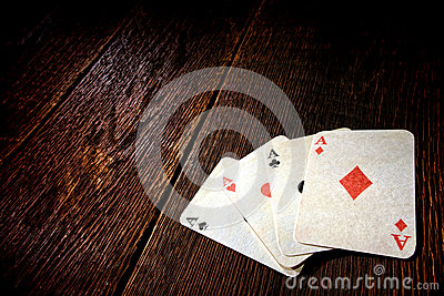 Four Aces Vintage Poker Cards on Old Saloon Table