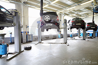 Four black cars on lifts in small service station.