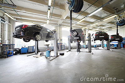 Four black cars on lifts in small service station