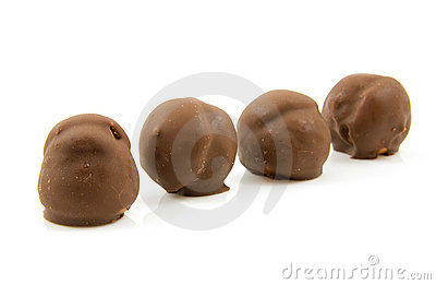 Four brown chocolate cream puffs in a row