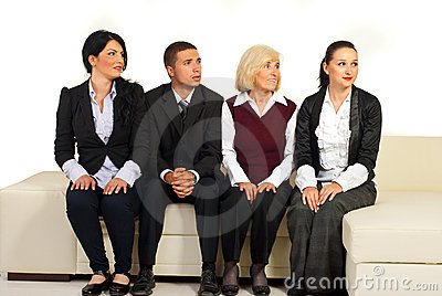 Four business people on sofa looking away