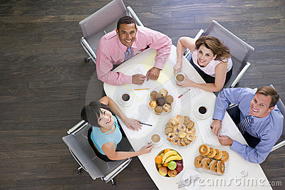 Four businesspeople eating at boardroom table