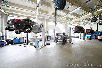 Four cars on lifts and on floor in small service station.